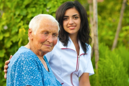 home nursing: A young doctor  nurse standing next to an elderly sick woman.