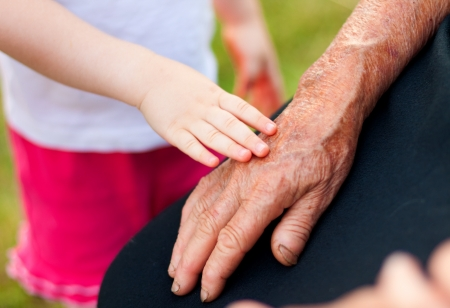 endearing: A little girl touching her grandmothers hand gently. Stock Photo