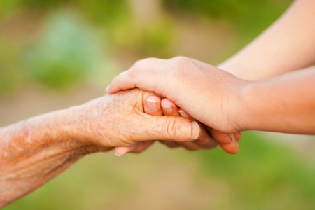 Young holding hand of an elderly woman outdoors. photo