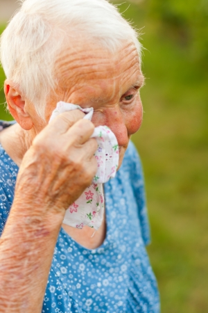 Old lady wiping her tears with a handkerchief.