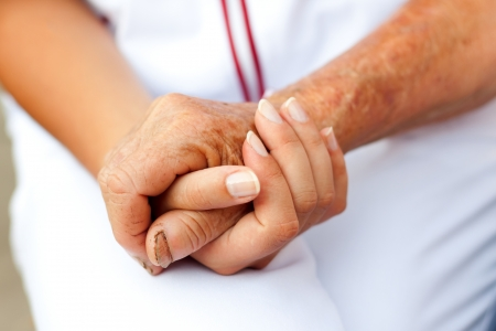 assisting: Doctor holding hand of an elderly woman Stock Photo
