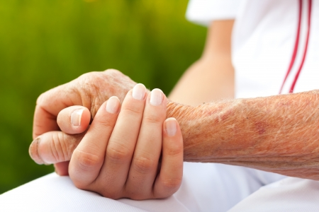 care at home: Doctor holding hand of an elderly woman Stock Photo