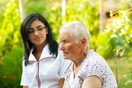 Old lady talking to the young nurse  doctor outdoors. photo