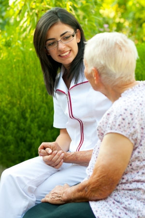 assisting: A young doctor  nurse visiting an elderly sick woman and chatting with her outdoors.