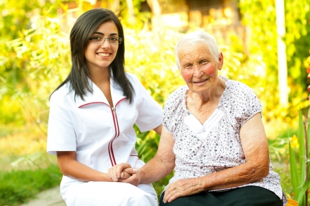 home health care: A young doctor  nurse visiting an elderly sick woman holding her hands with caring attitude.