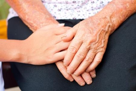 nursing aid: Young hands between elderly ones.