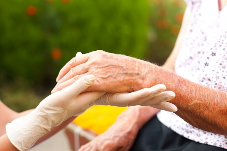 Doctor examining elderly womans hand at home.