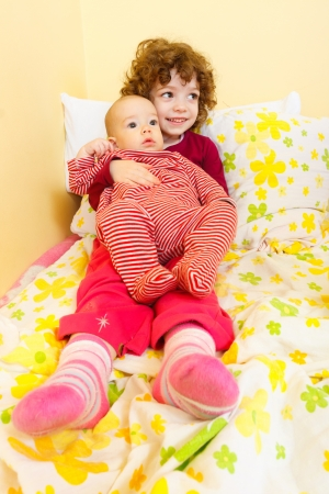 Little girl holding her baby brother on her lap. photo