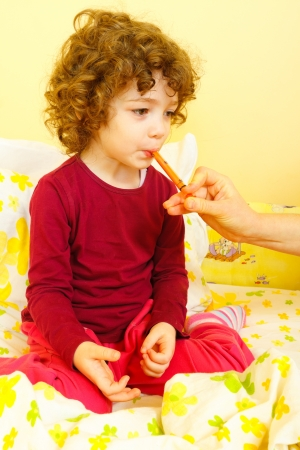 doses: Little sick girl in bed getting her medicine troughout a dosing syringe. Stock Photo