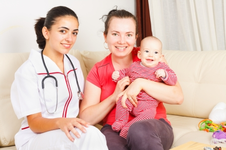 mother helping baby: Smiling mother with her happy son are sitting next to a kind nurse. Stock Photo