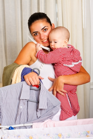 tasking: Baby helping her mother to talk on the phone while she is doing the laundry.