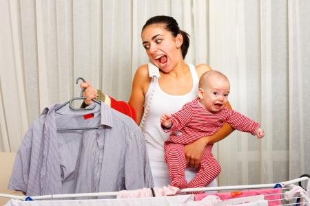 fille pleure: Crier jeune m�re marre de faire la lessive, tenant son enfant pleurer et parler au t�l�phone en m�me temps.