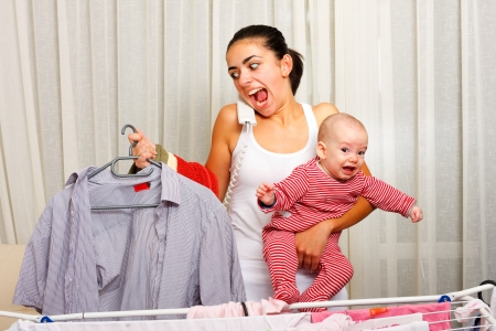 Screaming young mother fed up with doing the laundry, holding her crying child and talking on the phone in the same time. photo