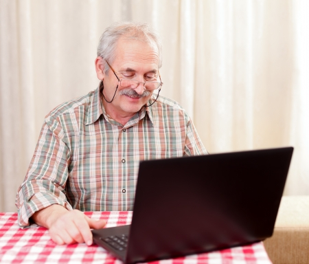 Elderly man using laptop at home at the table.