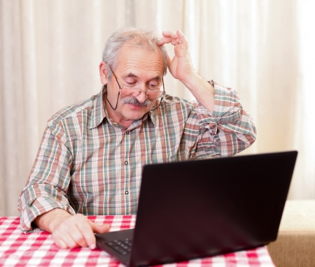 Elderly man using the laptop at home. photo