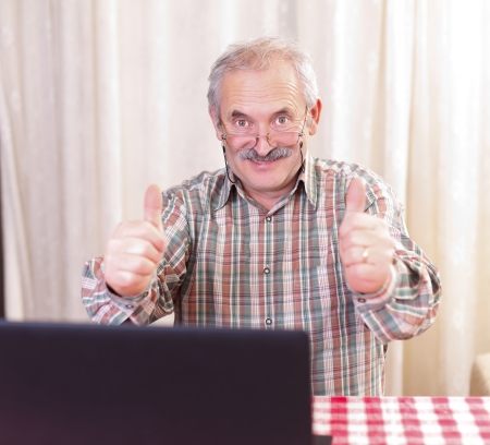 Elderly man with glasses using laptop at home. Stock Photo