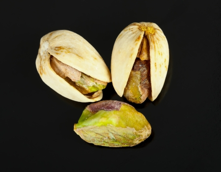 pistachios: Three dried pistachios isolated on black background.