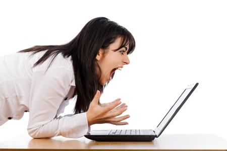 molesto: Mujer gritando nerviosamente en la computadora portátil aislados en blanco.
