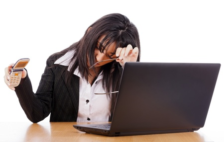 Woman tired of telephone calls hanging on and holding her head before laptop. photo
