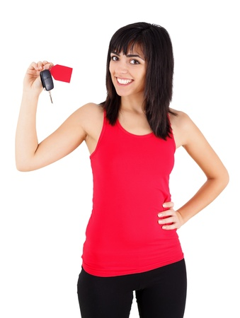 Confident young woman smiling happily with a new car key with tag in her hands - isolated on white. Stock Photo