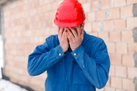 dissapointed: Dissapointed construction worker having a typical gesture: his face in his palms. Stock Photo