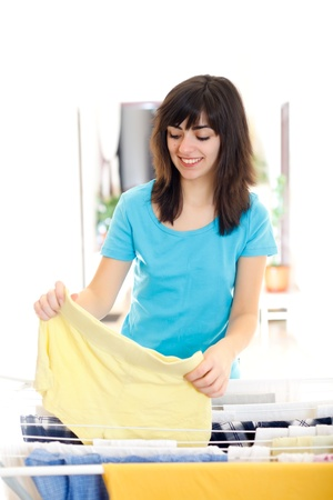 Happy beautiful housewife putting clothes to dry. photo