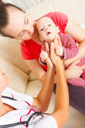 examined: Baby boy held by his mother examined by pediatrician. Stock Photo