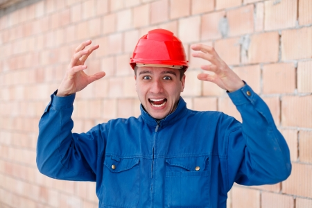 irritating: An angry construction worker having a funny reaction because of being behind schedule. Stock Photo