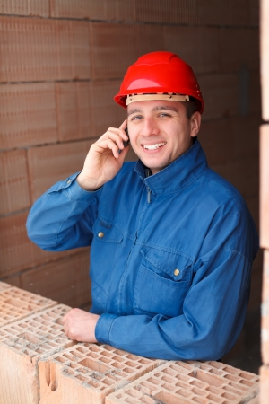 Happy constcuction woker  arhitect talking by phone with a cheerful facial expression. Stock Photo