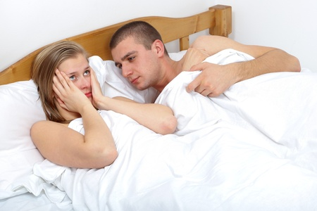 nude wife: Young couple lying in bed having sexual disfunction.