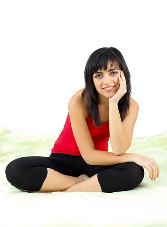 kindly: Smiling young woman looking kindly to the camera while sitting on bed.