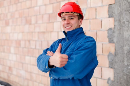 Happy construction worker showing thumbsup next to an unfinished  brick wall. photo