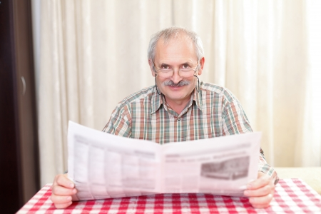 Elderly man reading the newspaper at home. photo