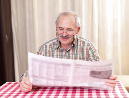 oude krant: Bejaarde man het lezen van de krant thuis. Stockfoto
