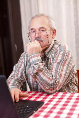 Elderly man with glasses using laptop at home. photo