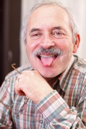 hombre disparando: Retrato de un hombre mayor divertido rodar su lengua.