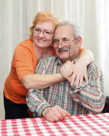 Elderly couple hugging each other at home. photo