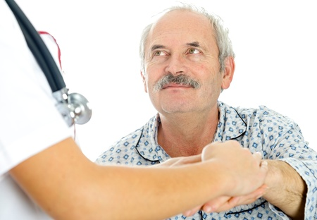 Doctor holding hand of senior man, patient looking at the doctor. photo