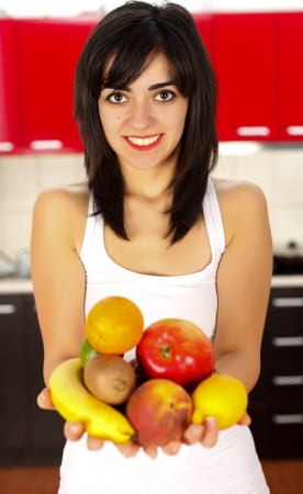commencing: Young woman holding a handful fruits commencing her diet.