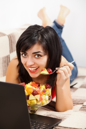 Smiling young woman laying in bed eating fruit salad in front of laptop. photo