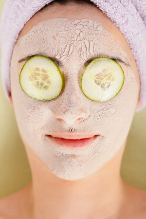 Woman at spa lying with clay mask on and cucumber on eyes. photo