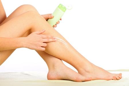 foot cream: Woman applying body cream on her legs.
