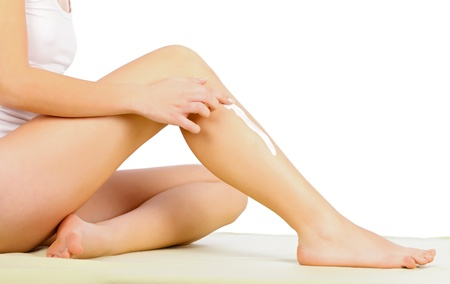 Young woman applying moisturizer on her leg. Stock Photo - 20794645