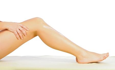 foot cream: Woman applying body cream on her leg isolated on white. Stock Photo