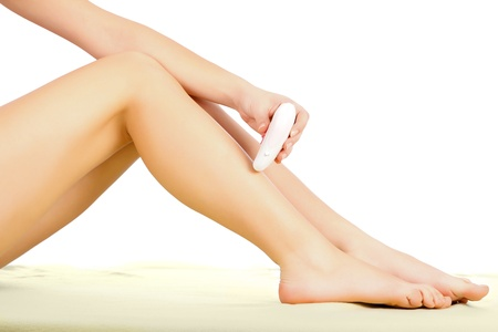 Woman using the epilator on her beautiful legs.   Stock Photo - 20794648