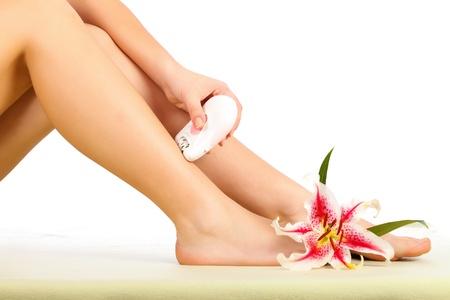 electric razor: Woman using the epilator on her beautiful legs.   Stock Photo