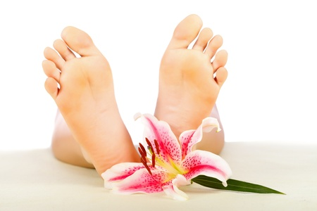 Woman feet with lily relaxing isolated on white. Stock Photo - 20794788