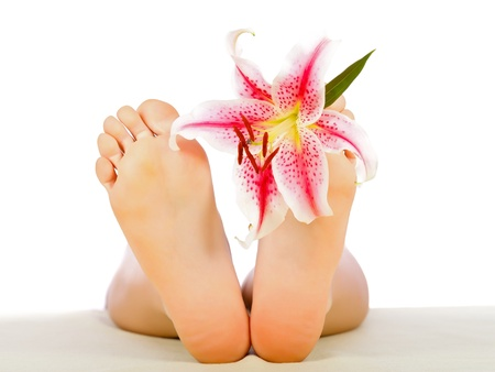 Woman feet with lily relaxing isolated on white. photo