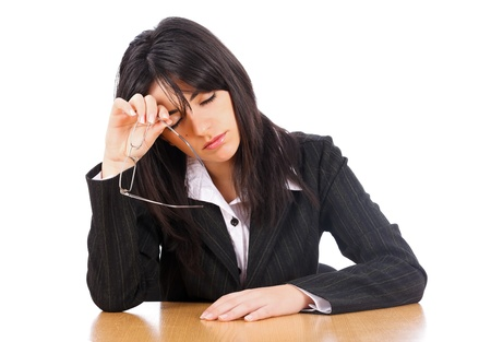 difficult task: Woman lawyer taking off her glasses sitting exhausted at her table.