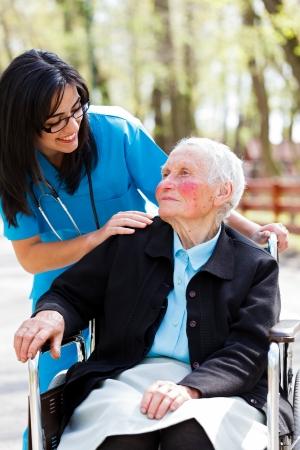 Beautiful doctor, nurse in blue coat walking a kind elderly lady in wheelchair in park. photo